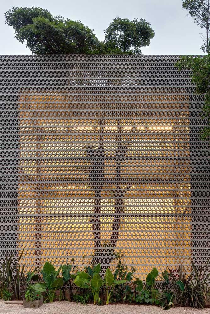 Muro alto de cobogos é puro charme e delicadeza; a proposta fica ainda mais bonita com a luz aos fundos