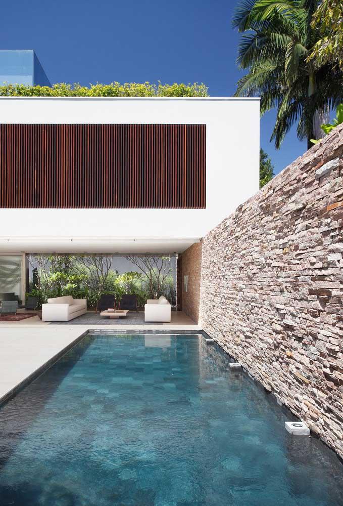Muro de pedras para garantir aquele visual especial na área da piscina