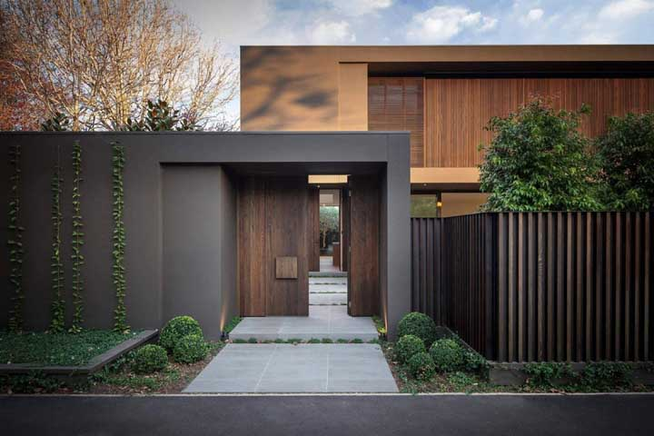 Entrada de casa sóbria e elegante com o muro de alvenaria e madeira em tom escuro