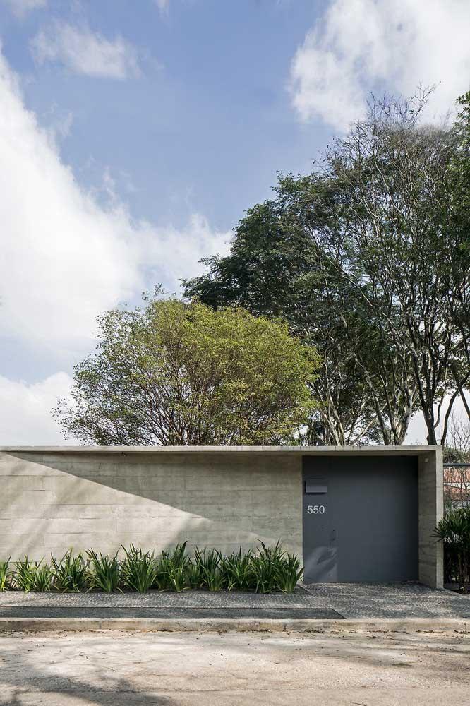 Muro com revestimento de pedra compartilha espaço com o portão fechado de aço