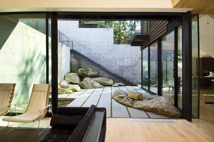 O muro de concreto aparente circunda a casa de paredes de vidro