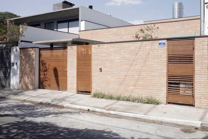 Muro de casa simples com portão social e portão de garagem; o diferencial está no revestimento de tijolinhos