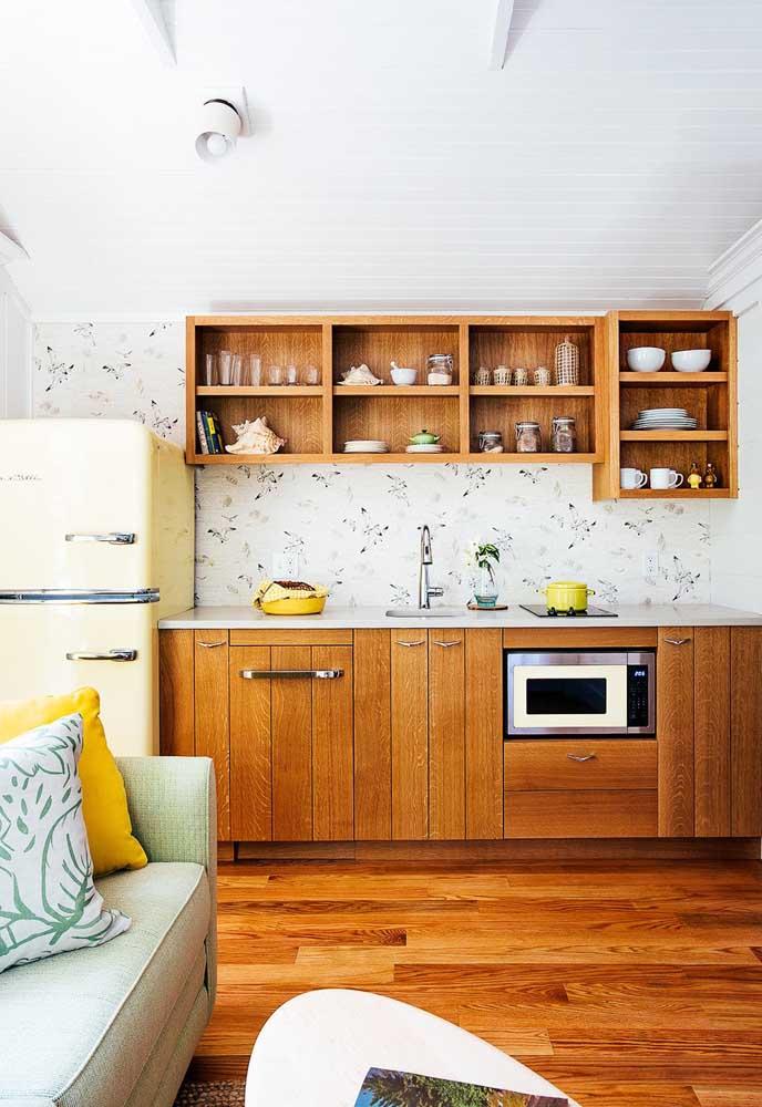 Uma cozinha com o piso e móveis de madeira precisa de papel de parede com um tom mais claro.
