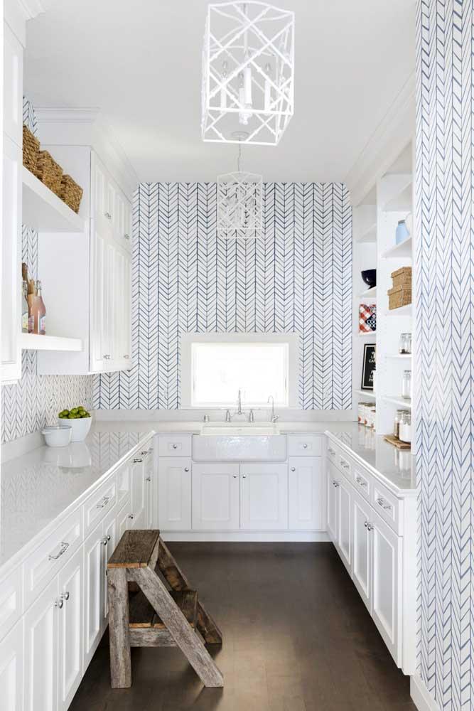 Você pode quebrar o branco total dos móveis da cozinha, apostando em um papel de parede que leva outra cor.