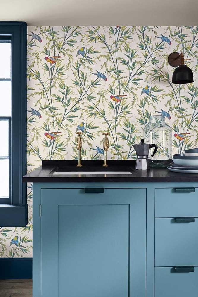 Um papel de parede com estampa de desenhos de floresta e animais fica excelente para combinar com móveis de diferentes tons azuis.