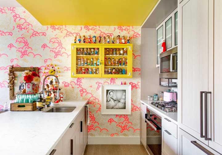 Quer brincar com as cores e estampas? Esse modelo de papel de parede faz com que a caixinha de bonecos se destaque ainda mais na decoração da cozinha.