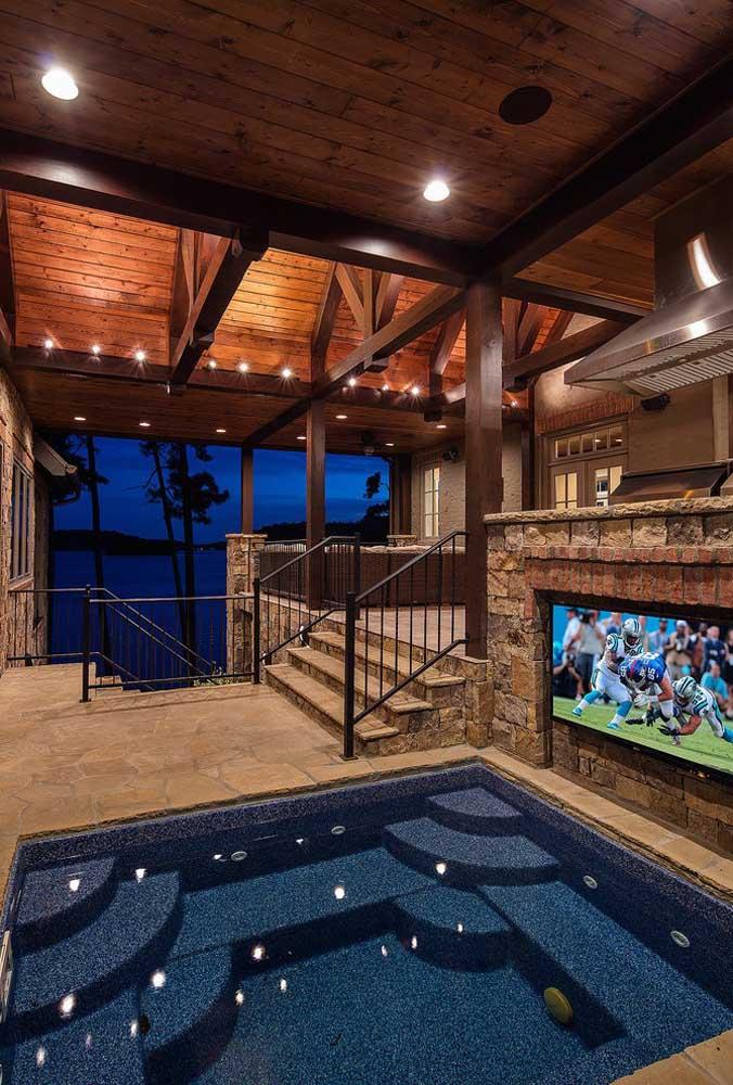 Olha que luxo é essa piscina dentro de casa. Para o espaço ficar mais aconchegante, instale uma TV no muro de pedra.