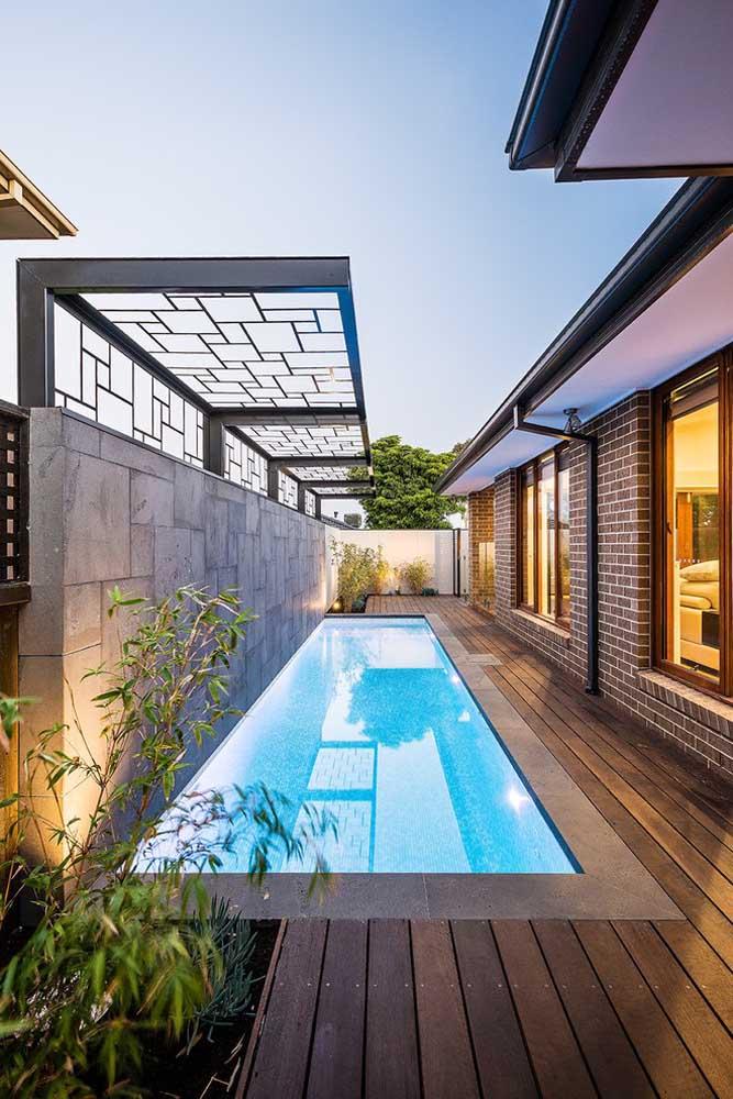 Mais uma piscina construída na lateral da casa. Apesar de ficar estreita, a piscina fica bem longa e a instalação do deck em toda área deixa o espaço mais charmoso.
