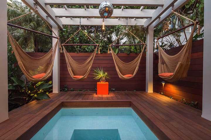Para quem deseja ter uma área de relaxamento dentro de casa, a piscina pequena com deck e as redes espalhadas ao redor são perfeitas.