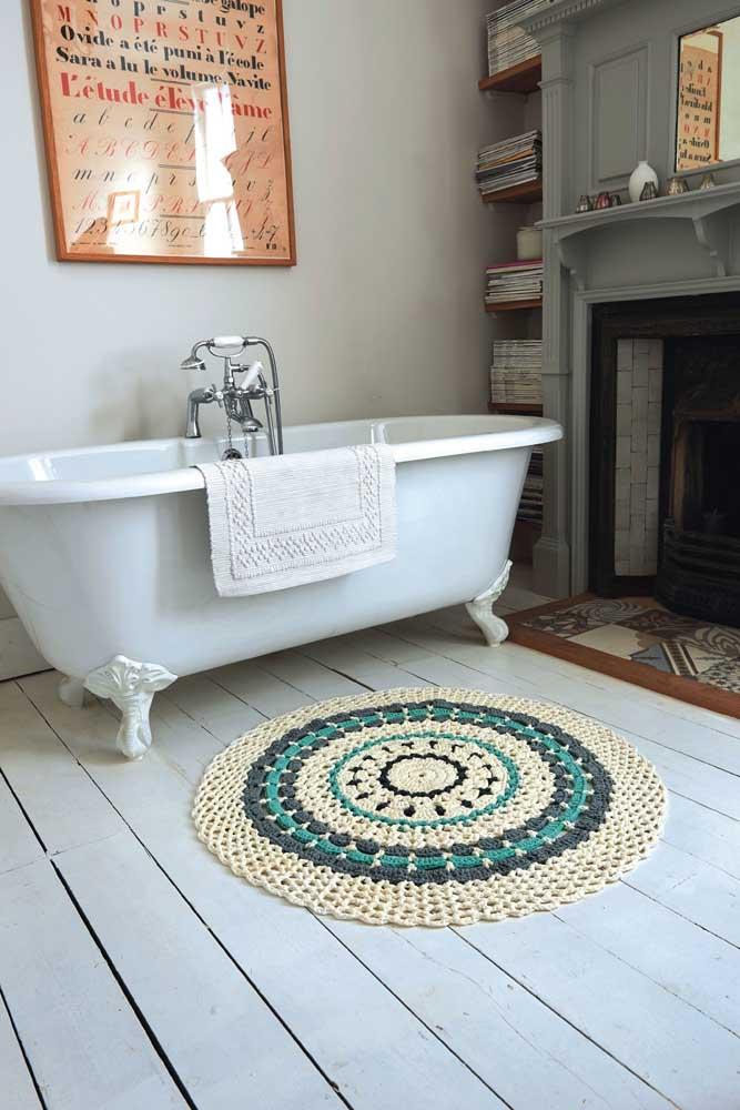 O banheiro de estilo retrô traz um tapete pequeno de crochê redondo para secar os pés de quem sai da banheira