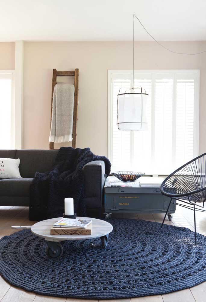 O azul escuro do tapete de crochê redondo traz elegância e sofisticação para a sala