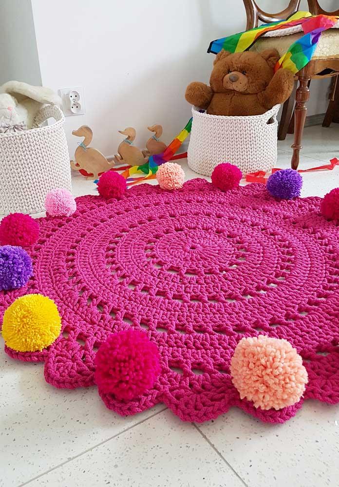 Os pompons coloridos garantem o aspecto lúdico e infantil desse tapete de crochê redondo