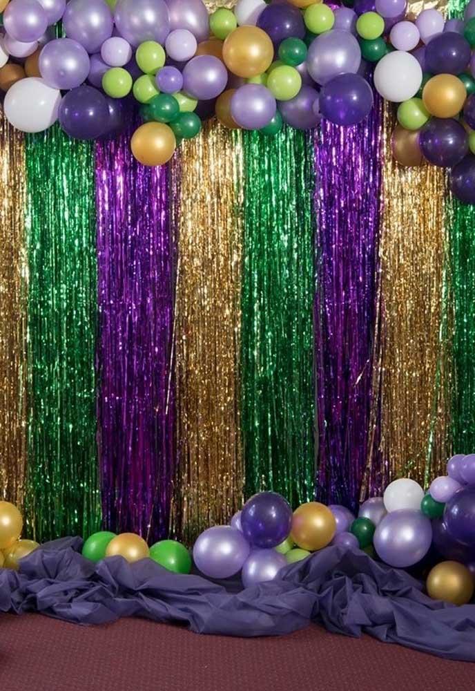 Que tal usar arcos de balões desconstruídos e misturar com uma cortina de fitas ou papel laminado?