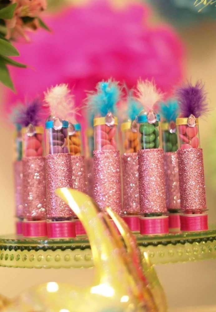 Para decorar as embalagens das guloseimas, use bastante glitter, fita e penas. Dê preferência às guloseimas coloridas para combinar com o tema.