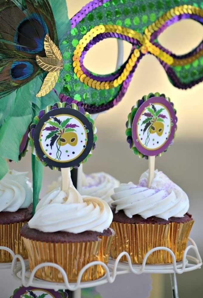 Coloque bastante chantilly no cupcake e por cima coloque um enfeite com o tema do carnaval.