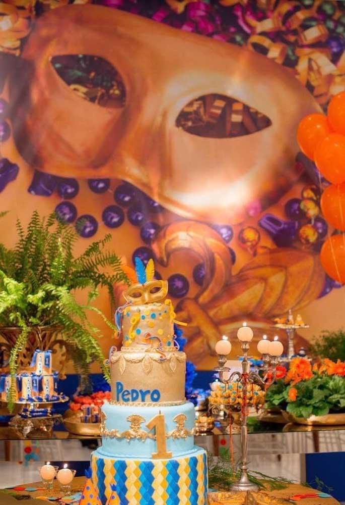 Agora se a intenção é fazer algo para chamar atenção, aposte no bolo fake com várias camadas. No fundo um belo painel com o tema carnaval.