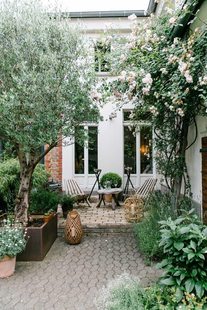 O jardim pequeno dessa charmosa área externa percorre as laterais, rente às paredes, deixando o centro livre