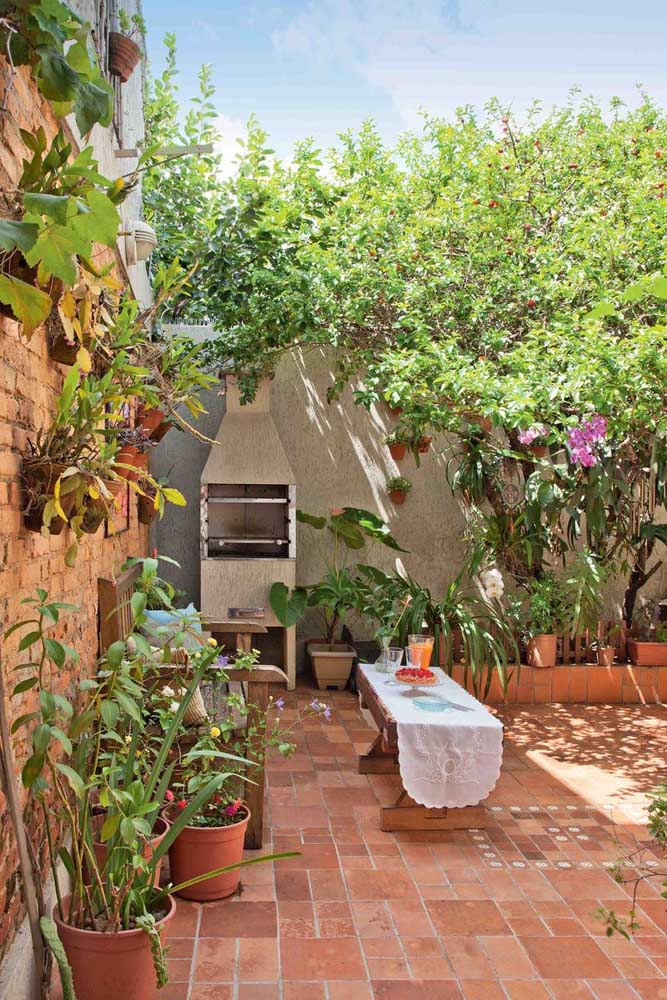 Linda área externa com jardim pequeno; espaço para churrasqueira e um pequeno banco para fazer a vez da mesa; na parede, as orquídeas se destacam