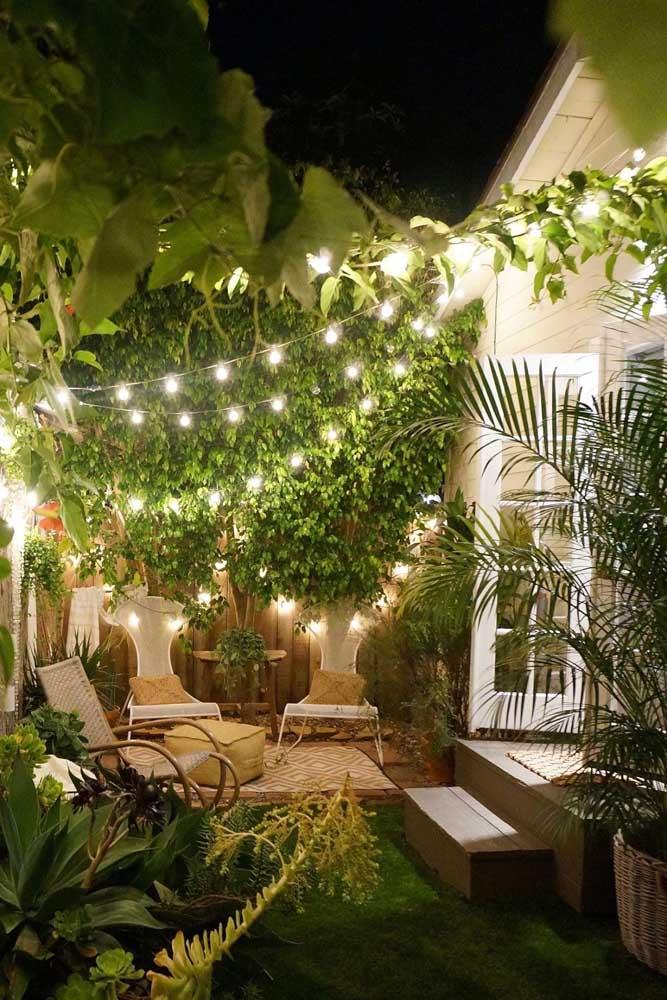 Aqui, a iluminação também se destaca, mas com o acréscimo de pequenos móveis para deixar o jardim mais confortável