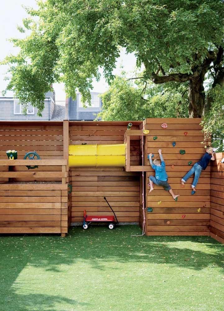 Jardim pequeno feito para as crianças, com espaço para parede de escalada e outras atividades