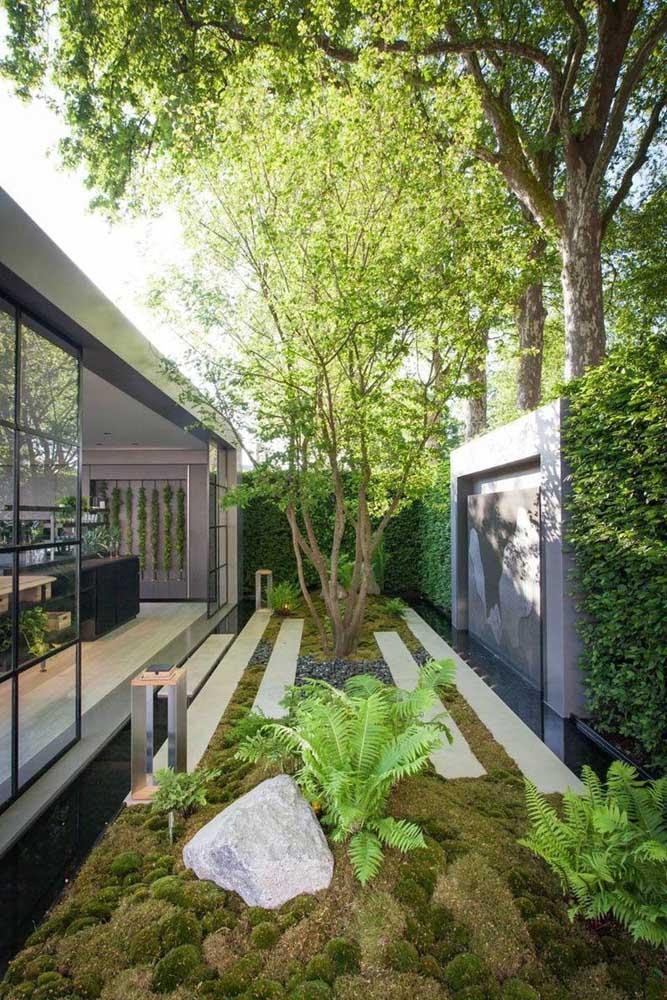 Um jardim moderno decorado com passante de concreto, pedrinhas e musgos