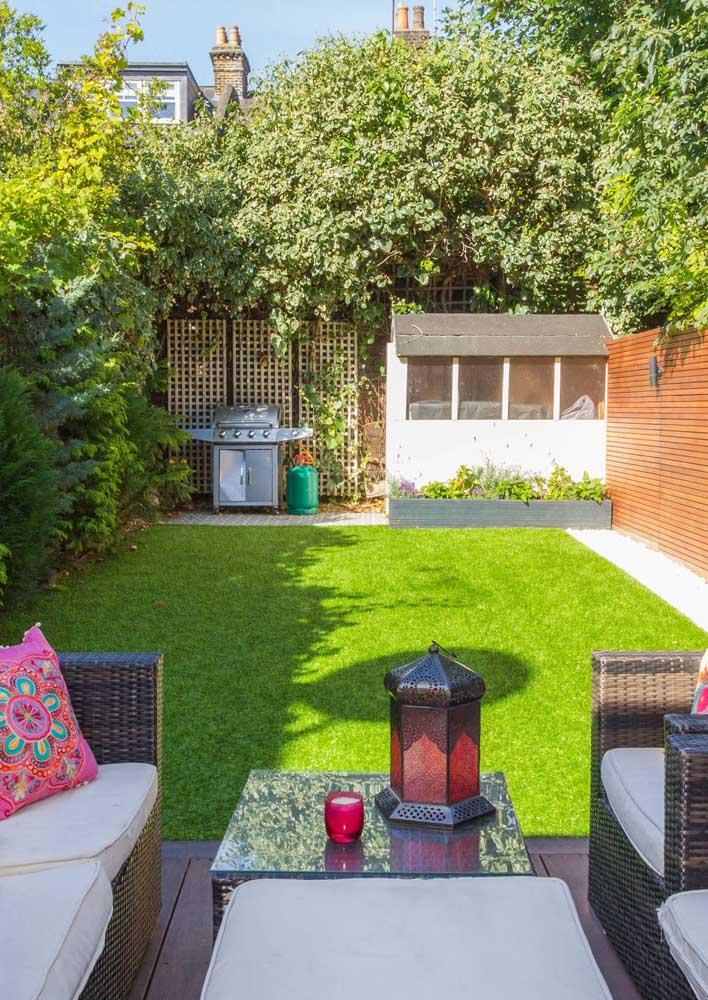 Entre o living e a pequena área gourmet está o gramado do jardim pequeno; a área verde se completa com o canteiro lateral