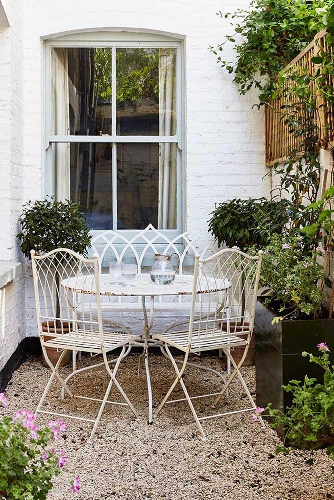 Os móveis de ferro garantem o romântico estilo shabby chic ao jardim pequeno
