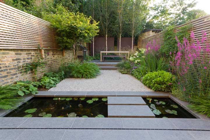 Flores e folhagens formam o canteiro lateral, enquanto o lago artificial faz a passagem para o interior do jardim