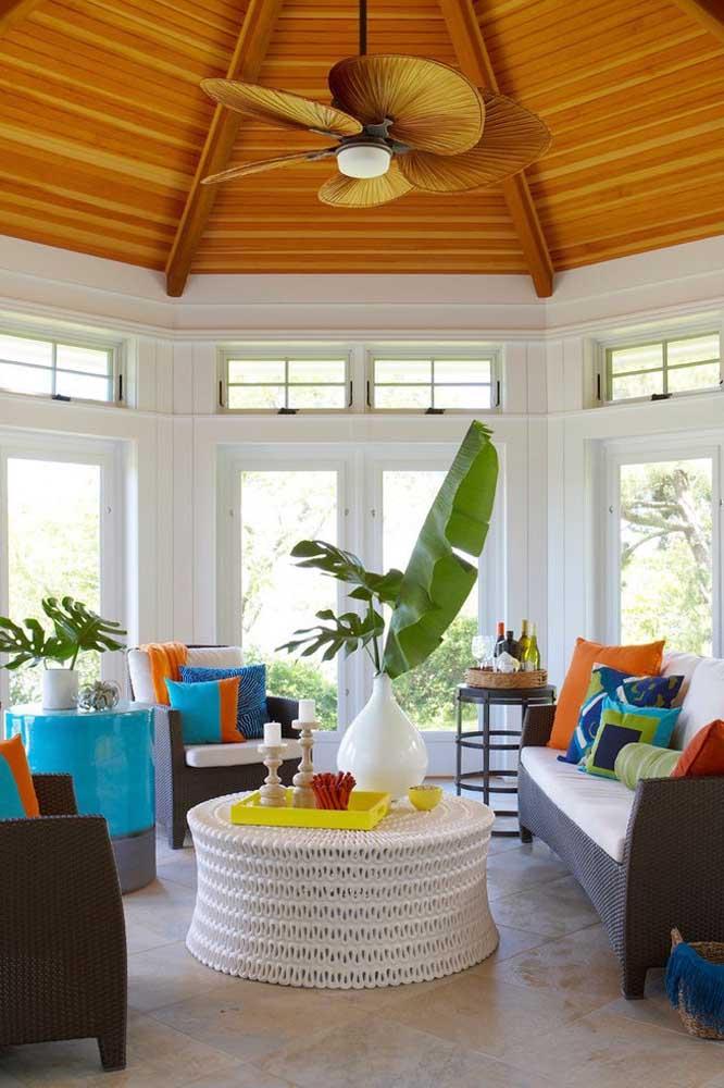Folhas grandes de plantas tropicais são o destaque desse vaso de cerâmica sobre a mesa de centro