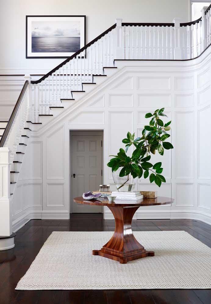 A decoração de base branca recebeu um belo contraste com o verde das folhas dentro do vaso de vidro; repare que o material do vaso segue a proposta leve e clean do ambiente