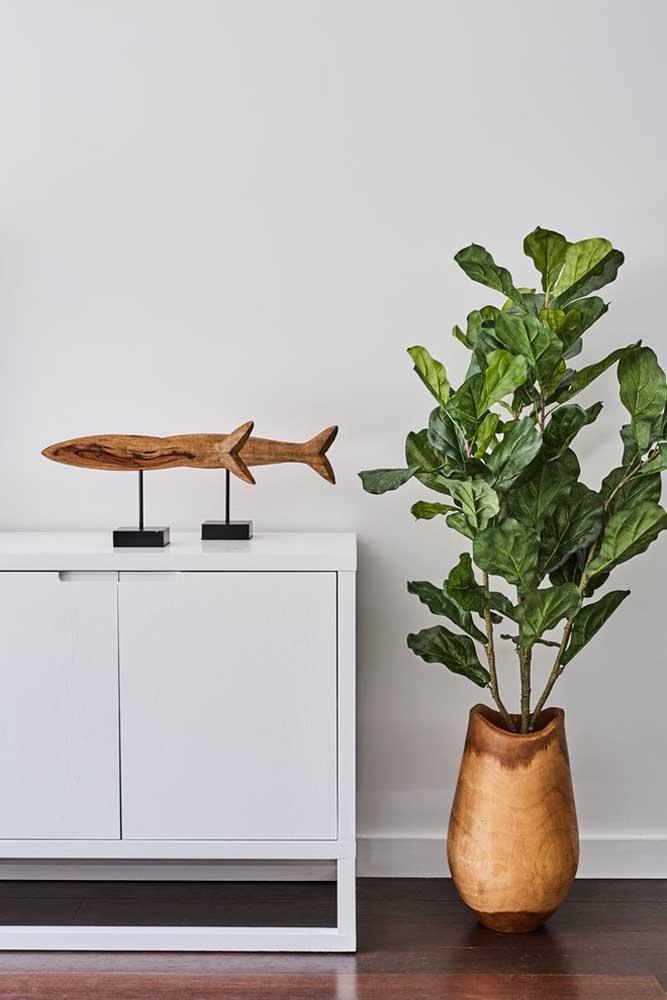 O vaso que abraça a figueira lira fala diretamente com o enfeite, também de madeira, sobre o aparador