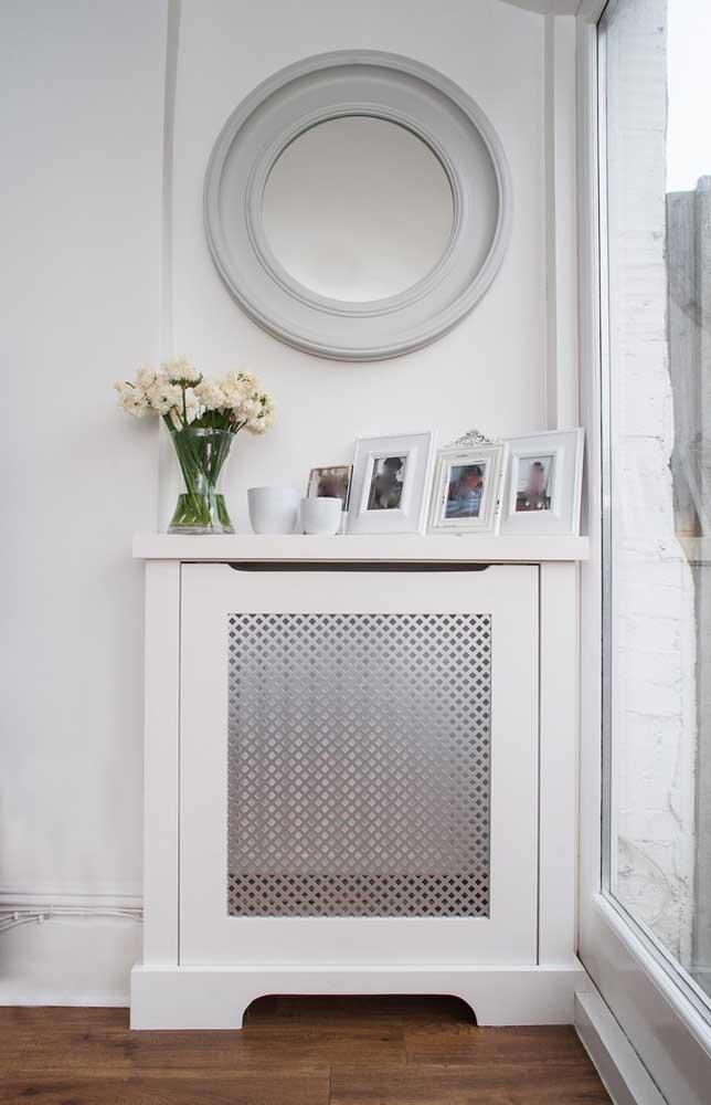 Junto às fotos, o vaso de vidro completa a decoração do aparador