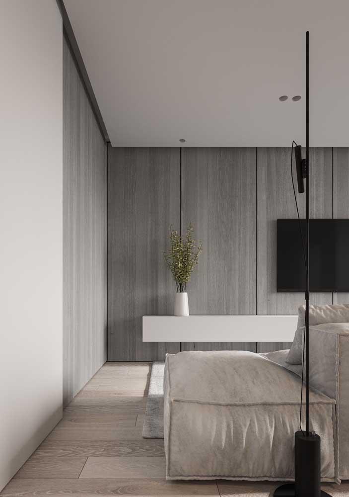O aparador branco suspenso dessa sala de estar se estende como se fosse também um rack; sobre ele, apenas um vaso discreto
