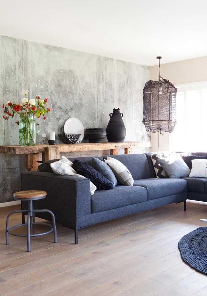 Aparador para sala de madeira rústica; repare no contraste entre o móvel e a parede de cimento queimado