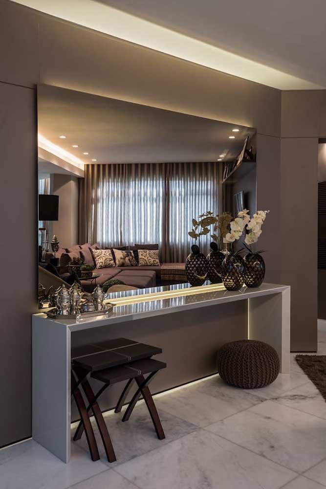 Aquele espaço vazio e sem graça da sala pode ser lindamente preenchido com um aparador; destaque para a iluminação sobre o móvel