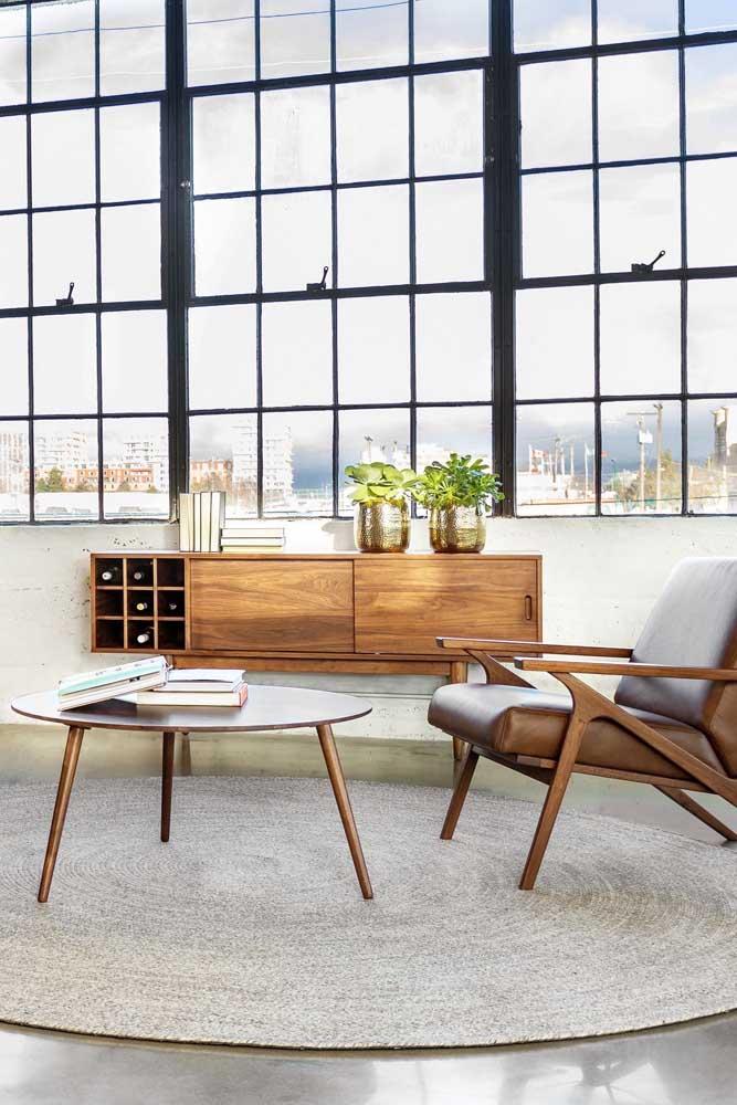 Aparador para sala de madeira com espaço para garrafas; repare que o móvel segue o mesmo tom da poltrona e da mesinha