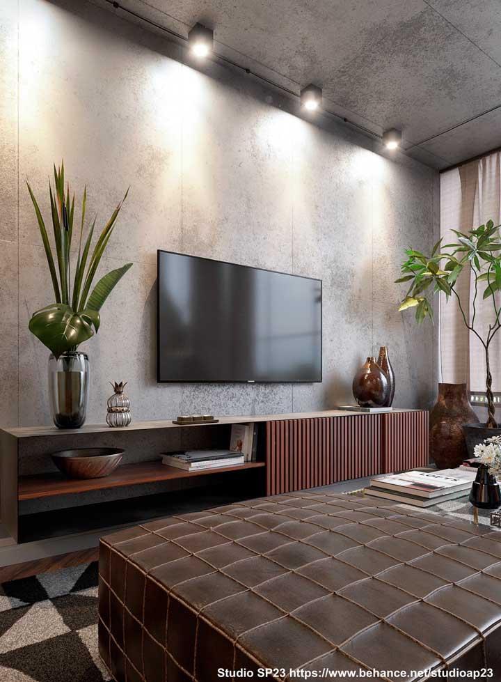 A elegância e sobriedade da madeira do aparador em contraste com o moderno e frio cimento queimado que reveste a parede e o teto