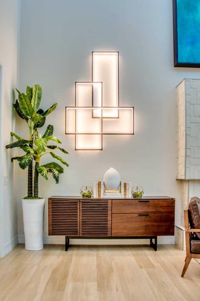 Quadro de luz reforça a presença do aparador nesse cantinho da sala de estar