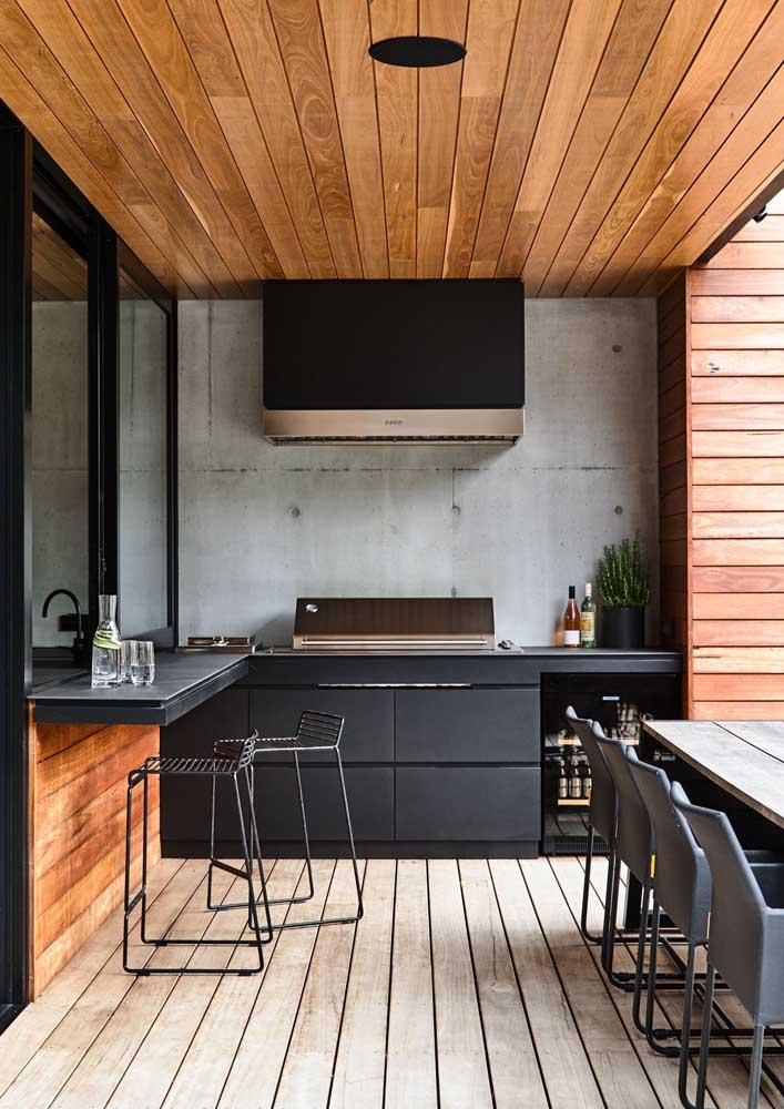 Aqui, os móveis pretos fazem um belo contraste com o piso e o forro de madeira