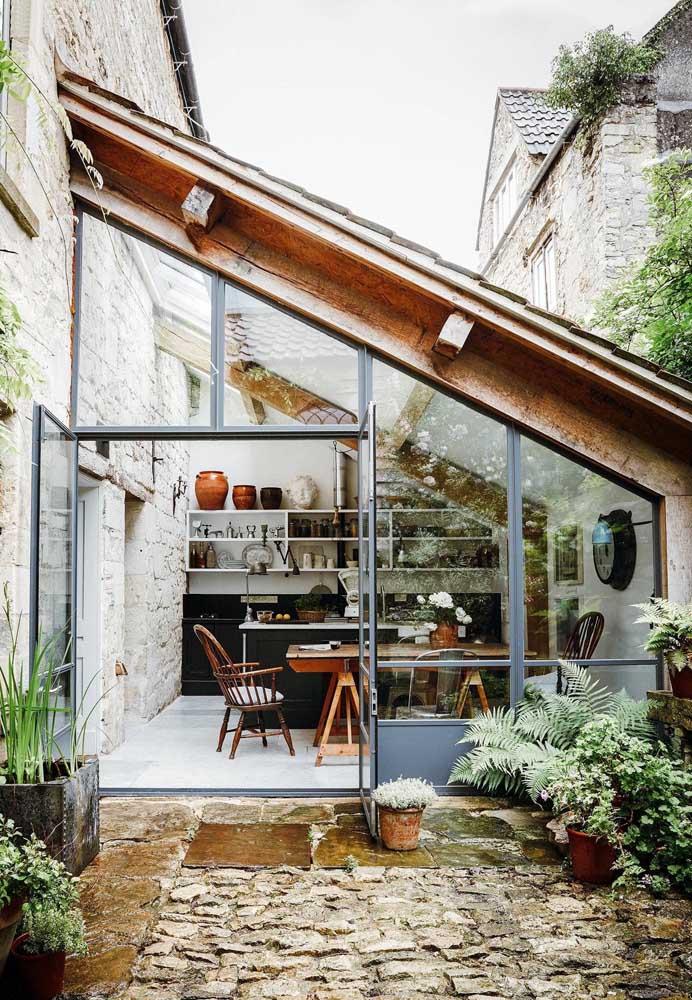 Essa área gourmet externa é integrada a parte interna da casa; a cobertura de vidro deixa o ambiente acolhedor e receptivo