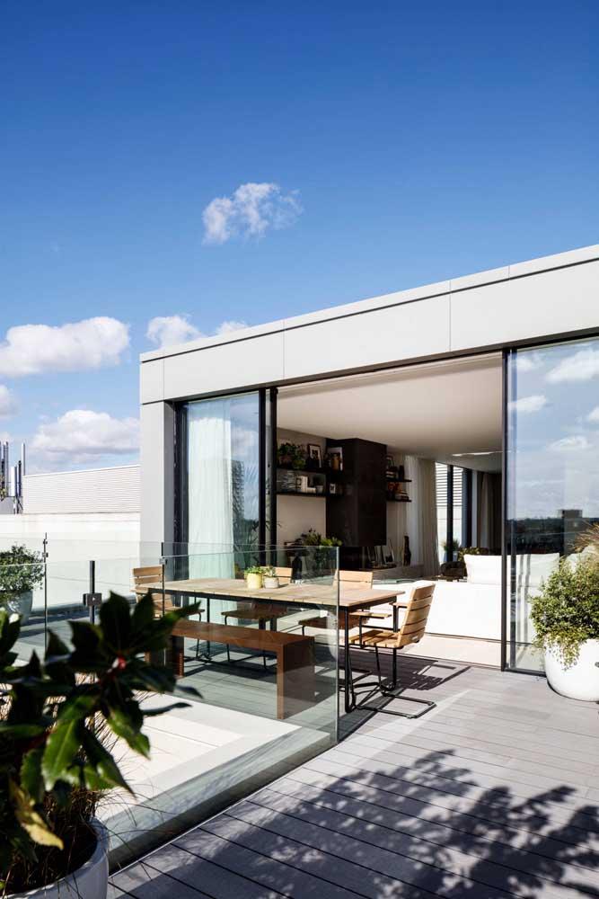 As portas de vidro de correr fazem a separação entra a área gourmet externa e o lado de dentro da casa