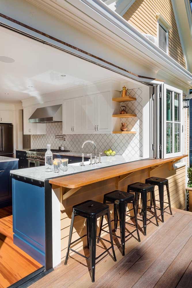 Integração total por aqui; quando a área externa não for utilizada basta dobrar o balcão para baixo e fechar o espaço com as janelas e a área gourmet volta a virar cozinha