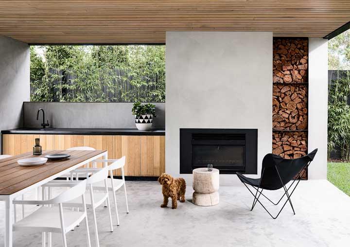 Área gourmet moderna e aconchegante; destaque para a lareira embutida na parede