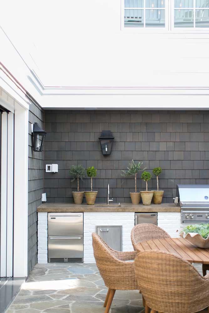 Nessa área gourmet, a bancada de tijolinhos e madeira realça os detalhes em aço inox