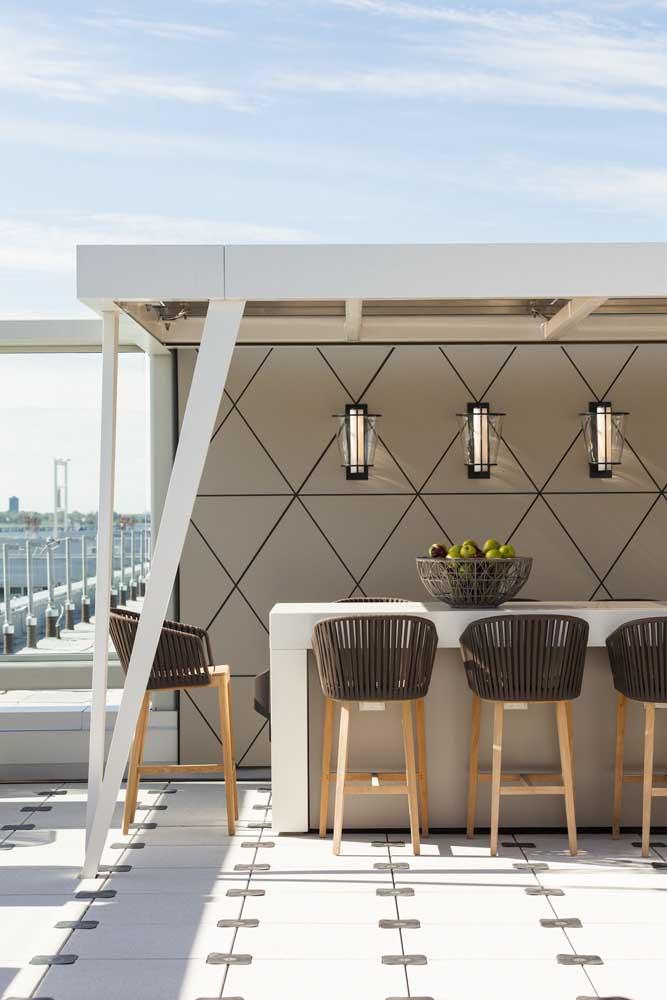 A cobertura sobre a mesa garante um refúgio do sol e da chuva; repare que a altura maior das cadeiras garante um clima despojado para a área gourmet