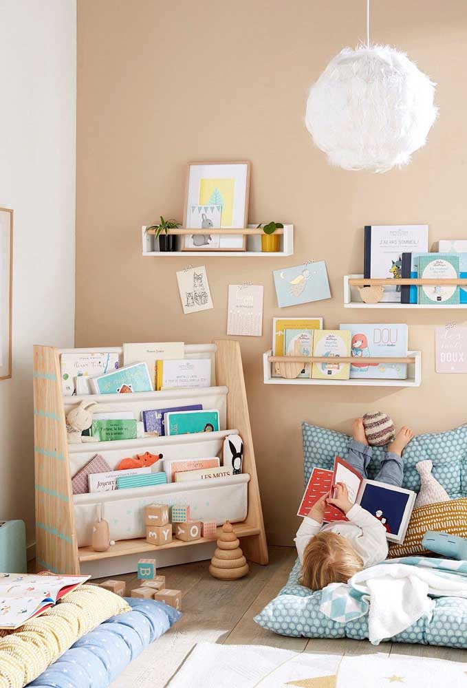 Modelo perfeito de cantinho de leitura infantil: o futon no chão dá total liberdade para a criança e os livros na estante baixa garantem a autonomia