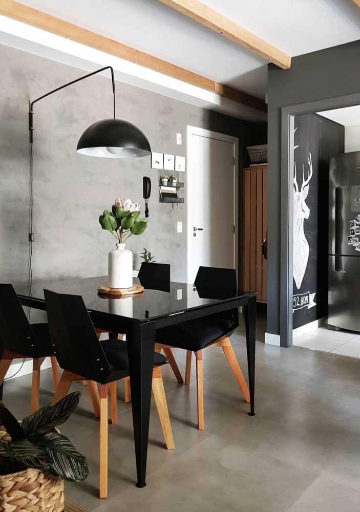 Outra combinação perfeita com o cimento queimado é usar móveis nas cores preta e amadeirado como nesse caso.