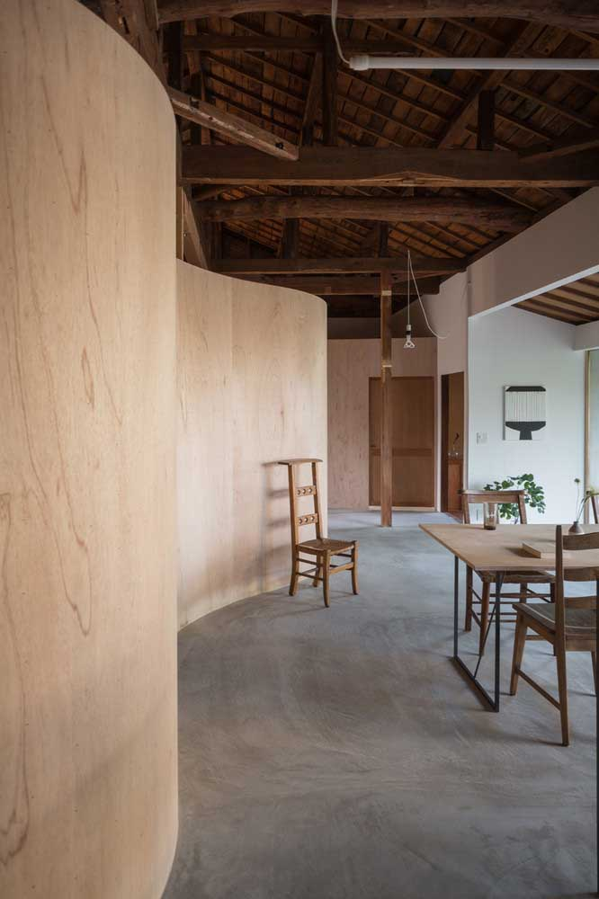 Uma mistura de sofisticação e modernidade do cimento queimado com um estilo mais rústico que está presente nos móveis, parede e teto do ambiente.