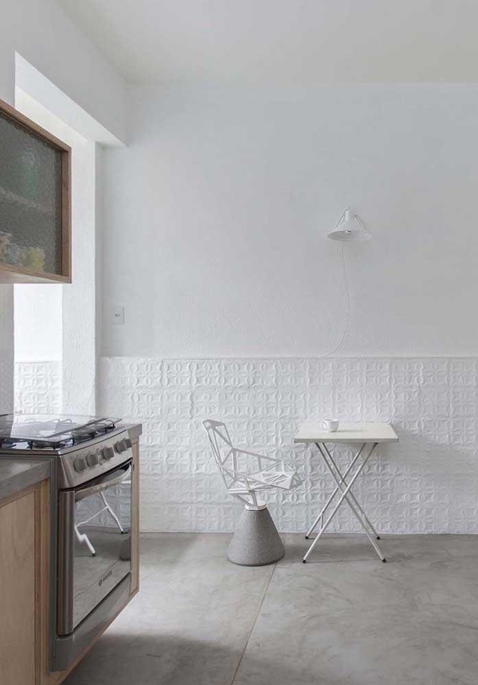 O contraste da parede branca com o piso feito de cimento queimado fica perfeito para decorar a cozinha.