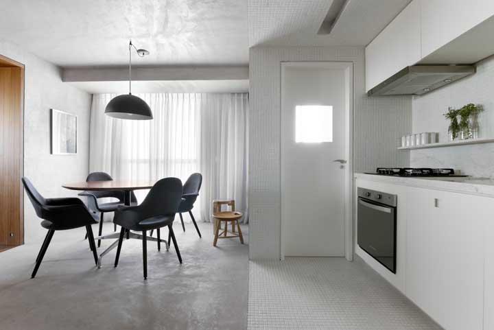 Para criar um ambiente mais minimalista, aposte no piso de cimento queimado, móveis nas cores preta e branca e parede totalmente branca.